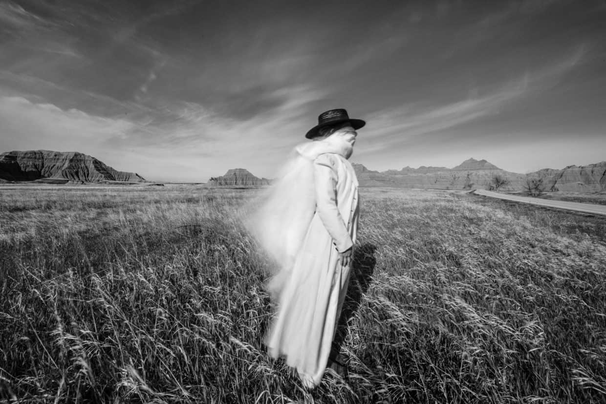 Stonetree Creative - Black and white fine art portrait of woman with face covered leaning into the wind
