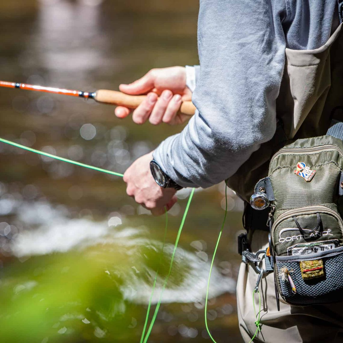 Man fly fishing in river in Maine - Stonetree Creative